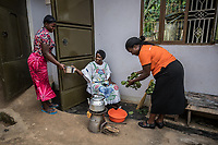 Uganda, Bujuuko. Jalia Musoke runs a tree farm and sewing business. She is busy with work and chores and uses a BioLite wood cook stove that she feels is faster than a regular cookstove. At home using her cookstove. With Judith Ocendi, a Brightlife senior sales agent.