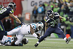 Seattle Seahawks running back Thomas Rawls (34) breaks the tackles of Carolina Panthers Carolina Panthers cornerback Robert McClain (27) and defensive end Kony Ealy (94) on his way to a 13-yard gain in the third quarter at CenturyLink Field in Seattle, Washington on December 4, 2016.  Rawls ran for 105 yards on 16 carries and scored two touchdowns in the Seahawks 40-7 win over the Panthers.  ©2016. Jim Bryant photo. All Rights Reserved.