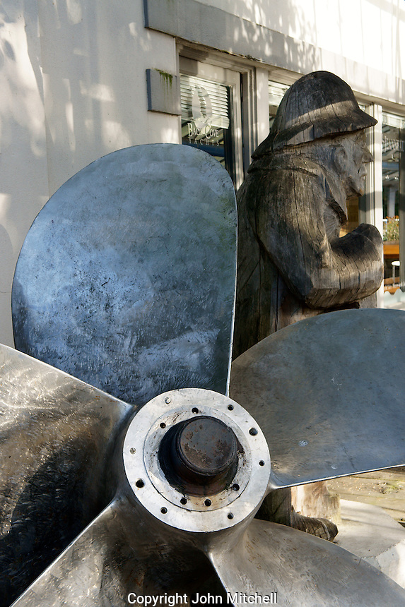 Close-up of a ship's propeller and carving of old sea captain , Granville Island, Vancouver, BC, Canada