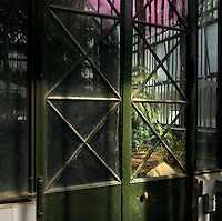 Plant History Glasshouse (formerly Australian Glasshouse), 1830s, Rohault de Fleury, Jardin des Plantes, Museum National d'Histoire Naturelle, Paris, France. Detail of glass and metal decorative door into the Plant History Glasshouse, lit by the afternoon sun. Through the door the luxuriant Tropical foliage is visible.