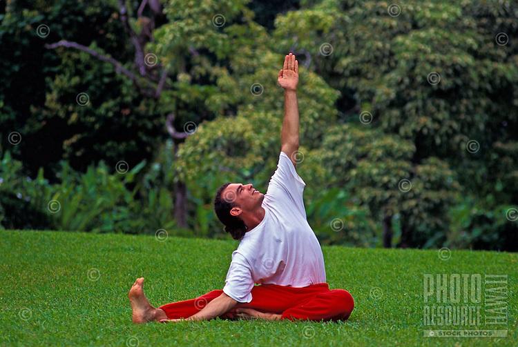 Man practicing yoga on a green lawn in Hawaii.