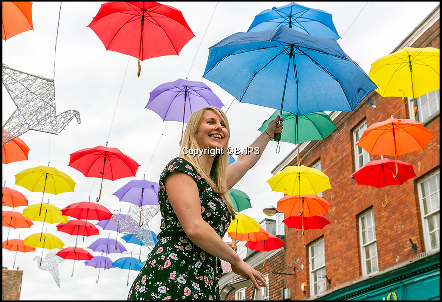 BNPS.co.uk (01202 558833)Pic: LeeMcLean/BNPS<br /> <br /> Marketing & Communications Manager at Salisbury District, Kara Rogers, adding the finishing touches to a special art installation featuring 90 umbrellas in the heart of Salisbury.<br /> <br /> A special art installation featuring 90 umbrellas has been erected in Salisbury to attract visitors as the beleaguered city attempts to recover after the devastating poisoning fall out.<br /> <br /> The multicoloured brollies have been hung 15ft above the High Street and will be in place until the autumn.<br /> <br /> They shelter 10 illuminated doves which send a message of 'hope and peace' in the aftermath of the deadly Novichok nerve agent attacks in March.