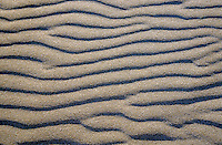 Patterned waves in white sand.