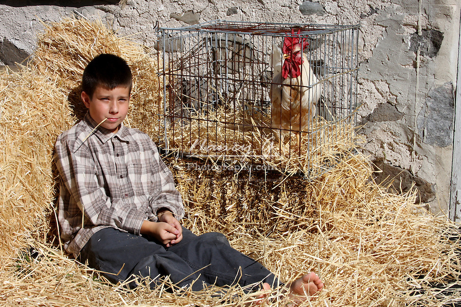 A young boy with his rooster next to a stone wall barn