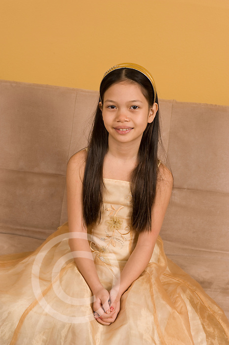 9 year old girl portrait in dressy dress stains on couch behind her mimicking angel wings vertical