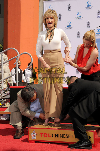 Jane Fonda.TCM Classic Film Festival 2013 - Jane Fonda Handprint and Footprint Ceremony held at the TCL Chinese Theatre, Hollywood Walk of Fame, Hollywood, California, USA, 27th April 2013..full length white top leopard animal print scarf beige brown trousers high waisted pulling up feet foot prints standing in cement .CAP/ADM/BP.©Byron Purvis/AdMedia/Capital Pictures