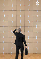 Businessman facing a cardboard boxes wall (Licence this image exclusively with Getty: http://www.gettyimages.com/detail/109862340 )