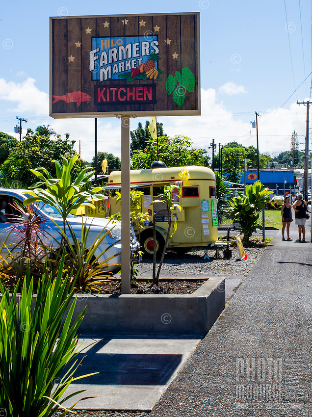 A yellow lunch wagon near the Hilo Farmers Market Kitchen sign on Mamo Street in downtown Hilo, Big Island of Hawai'i.