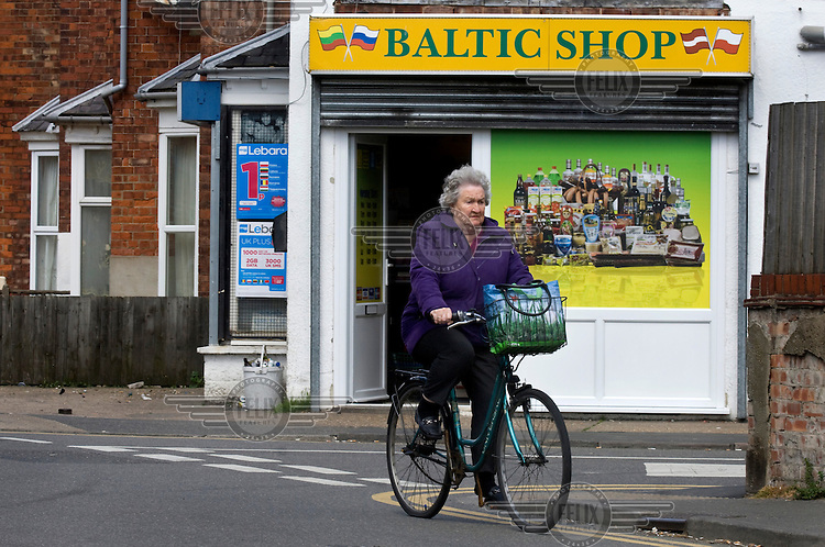 A woman cycles past an Eastern European food store in a residential street near Boston town centre. Large migrant European communities live locally and work in the agriculture, horticulture or service sectors.