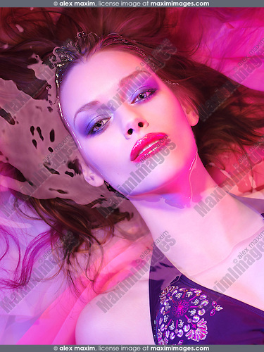 Beautiful woman lying in water wearing makeup under vivid pink purple colorful light. Conceptual closeup beauty face portrait.