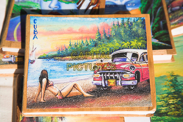 Painting of car and woman on photo album on market stall in the Craft Market, Guardalavaca, Holguin Province, Cuba