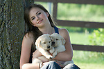 Teenage girl holding two yellow Labrador retriever (AKC) puppies