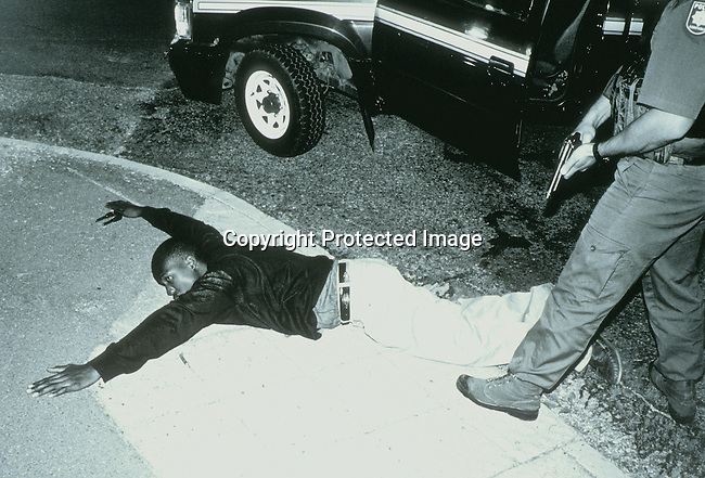 pspolic27167.Police.A suspected car thief has been stopped on November 23, 1998 by an unidentified member of the Flying Squad a rapid response unit in Johannesburg, South Africa. South Africa has one of the highest crime rates in the world; policeman holding a gun, pointed at a suspect lying on the ground..©Per-Anders Pettersson/iAfrika Photos