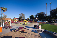 An overview of Circle Park, a pocket park located on Park Circle Drive in Anaheim, California.  This is a relatively wide-angle view of the park that places the park in the context of its surrounding parking and apartments.  Visible are play structures, an artificial-turf lawn, benches, a picnic / BBQ area, a red fence, and more.