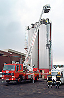 Hydraulic platform fire engine performing a rescue from a silo. The firefighters are in the cage at the end of the boom and will manoeuvre it towards the roof of the silo where the other firefighters and paramedic ambulance crew are attending to victims injuries. The workman fell down into the sugar silo and was knocked unconscious. The firefighters, wearing breathing apparatus, had to absail down inside the silo and haul him out by means of a rope sling...© SHOUT. THIS PICTURE MUST ONLY BE USED TO ILLUSTRATE THE EMERGENCY SERVICES IN A POSITIVE MANNER. CONTACT JOHN CALLAN. Exact date unknown.john@shoutpictures.com.www.shoutpictures.com..