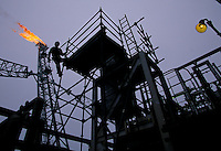 Scaffolding crew works to erect scaffold to inspect welds....Site is so safety conscious they will erect scaffold to change a light bulb.  Flare boom in background is burning off excess natural gas.  Soon this gas will be redirected back into the well to store for future use and provide pressure to force the oil to the surface.