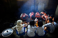 "Students of Kartini Emergency School build a fire to be used for cooking. As part of the ""life skills"" training, teams of students are formed, so that each child has a chance to learn to cook for the school Since the early 1990s, twin sisters Sri Rosyati (known as Rossy) and Sri Irianingsih (known as Rian) have used their family inheritance to set up and run 64 schools in different parts of Indonesia, providing primary education combined with practical skills to some of the country's most deprived children."