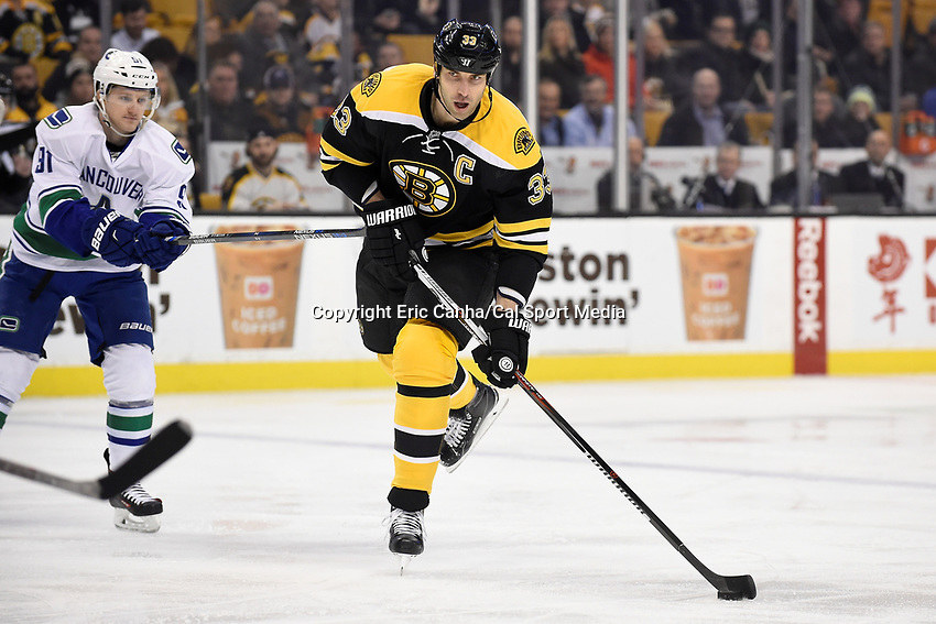 Thursday, January 21, 2016: Boston Bruins defenseman Zdeno Chara (33) plays the puck at the blue line as Vancouver Canucks center Jared McCann (91) tries to stick check during the National Hockey League game between the Vancouver Canucks and the Boston Bruins, held at TD Garden, in Boston, Massachusetts. Eric Canha/CSM