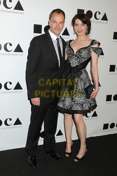 Jonny Lee Miller and Michele Hicks.2011 MOCA Gala - An Artist's Life Manifesto held at MOCA Grand Avenue,  Los Angeles, California, USA, .12th November 2011..full length black suit tie bow dress silver  open toe shoes clutch bag  .CAP/ADM/BP.©Byron Purvis/AdMedia/Capital Pictures.