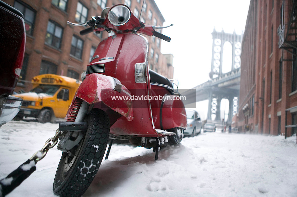 14 February 2007 - New York City, NY - A scooter stands in the snow in Brooklyn, New York City, USA, as the first snow storm of the year hits the city, 14 February 2007. The Manhattan Bridge is seen in the background.
