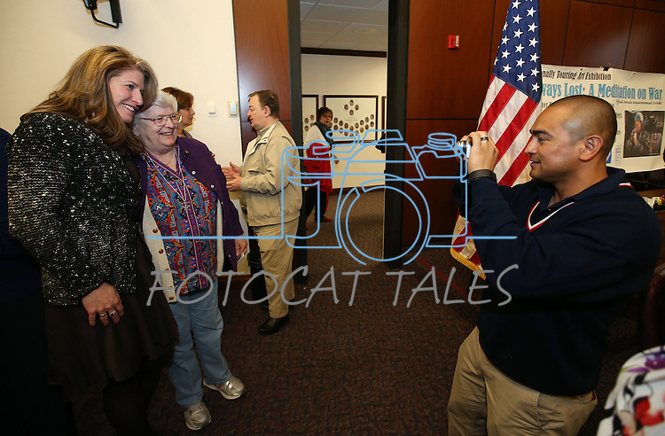 Amy Roby, project manager of the Always Lost: A Meditation on War exhibit poses with Navy veteran Ellie Hays and her godson Marine Master Sgt. Carlos Candido at the Legislative Building in Carson City, Nev., on Monday, April 6, 2015. <br /> Photo by Cathleen Allison/Nevada Photo Source