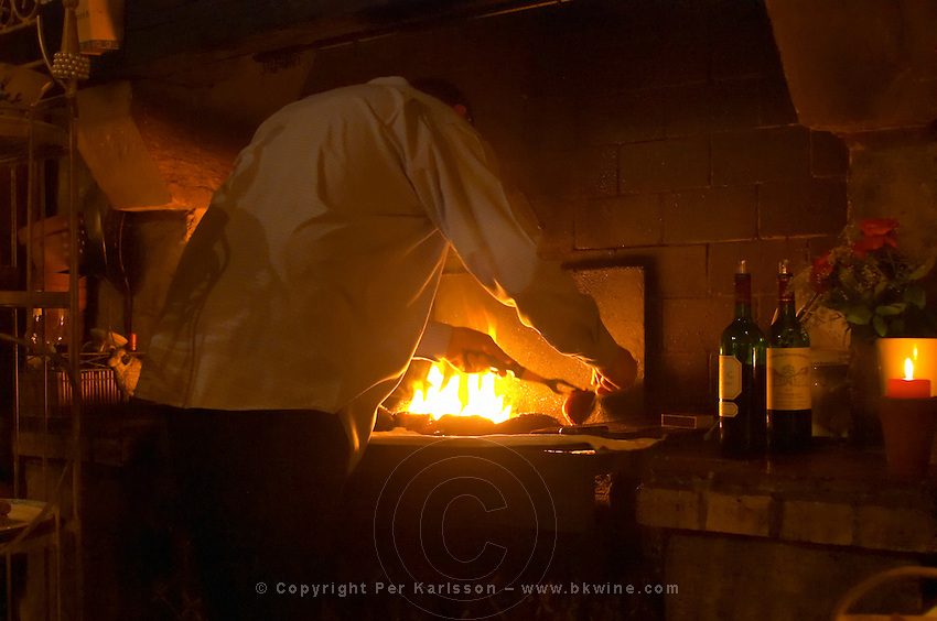The fireplace used for preparing food, with ducks' breasts being grilled, the cook chef turning the food on the barbecue at the gastronomic restaurant L'Enfance de Lard Bergerac Dordogne France