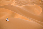 A man sits alone on the sand dunes of the Empty Quarter, Ar Rub Al Khali, Oman.