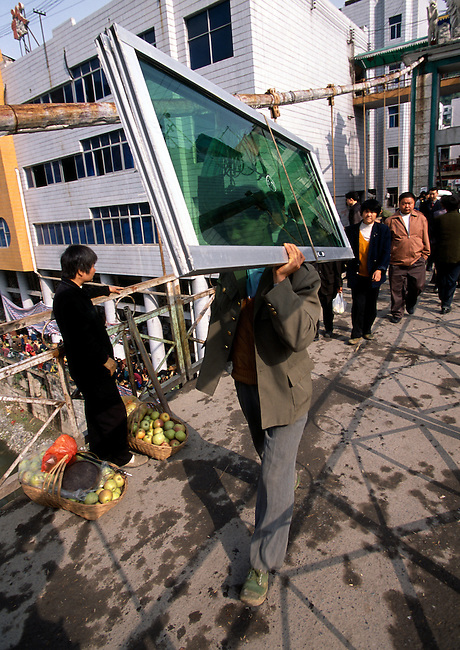 Man carrying sliding glassdoors across bridge; transport; commerce; morning in town of Wuxi, China, Asia; 042503