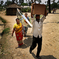 The Luiter family, who finished third in a solar-powered cooking competition, carry home a solar cooker and several insulated food storage boxes. All the entrants were given a solar cooker to take home with them after the event and the winner received a pressure cooker. With the financial help of the Dutch Council for Refugees, a total of 6,300 solar cookers will be distributed amongst the Bhutanese refugees living in the region. The solar cookers consist of a reflective, aluminium, parabolic-shaped device that concentrates the sun's rays onto cooking pots placed on a frame in the centre of the dish. The dish has to be adjusted to the new position of the sun around every 10 minutes. It takes about 55 minutes to prepare a cooked meal on a sunny day and it is hoped that using the solar cookers will alleviate pressure on resources and reduce kerosene consumption by 75%...
