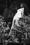 Black and white portrait of a young woman in a white summer dress sitting on the edge of balcony railings in a garden enjoying sunshine in spring