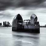 Thames Barrier, london with Canary Wharf in background under grey sky