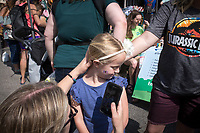 NWA Democrat-Gazette/CHARLIE KAIJO Tiffany Severs takes a picture of Lily Severs, 5, of Bella Vista after having her face painted, Saturday, May 12, 2018 at the Town Square in Bentonville. <br />