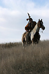 A Native American Indian man sitting bareback on a horse leaning forward in traditional Sioux Indian clothing in South Dakota
