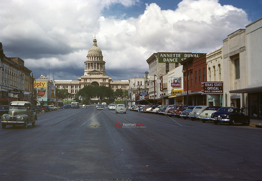 In this historical 1950 photo, cars line up and down Congress Avenue in front of the downtown retail stores including Texas State Optical, Annette Duval Dance Studio, Prices, Studer Photo Co. and Greenwood Drugs leading up to the Texas State Capitol in Austin, Texas.