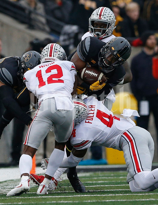 Ohio State Buckeyes cornerback Denzel Ward (12) and Ohio State Buckeyes cornerback Jordan Fuller (4) tackle Iowa Hawkeyes running back Akrum Wadley (25) during the first quarter of a NCAA college football game between the Iowa Hawkeyes and the Ohio State Buckeyes on Saturday, November 4, 2017 at Kinnick Stadium in Iowa City, Iowa. [Joshua A. Bickel/Dispatch]