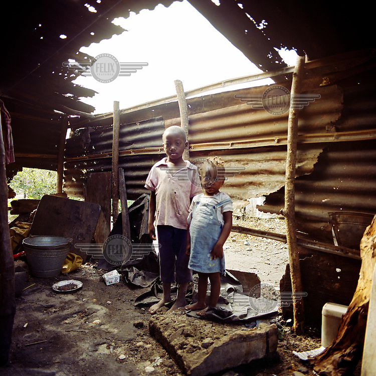 Joao and his sister Cacilda standing in their home where they live with their mother Domingas who is HIV positive. Their father died a few years ago; he was also HIV positive. Since then they have been living in extreme poverty..