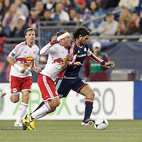 New England Revolution substitute midfielder Juan Toja (18) dribbles as New York Red Bulls midfielder Teemu Tainio (6) pressures. Despite a red-card man advantage, in a Major League Soccer (MLS) match, the New England Revolution tied New York Red Bulls, 1-1, at Gillette Stadium on September 22, 2012.