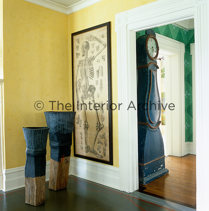 A lifesize anatomical drawing and a pair of sculptures in the corner of the living room
