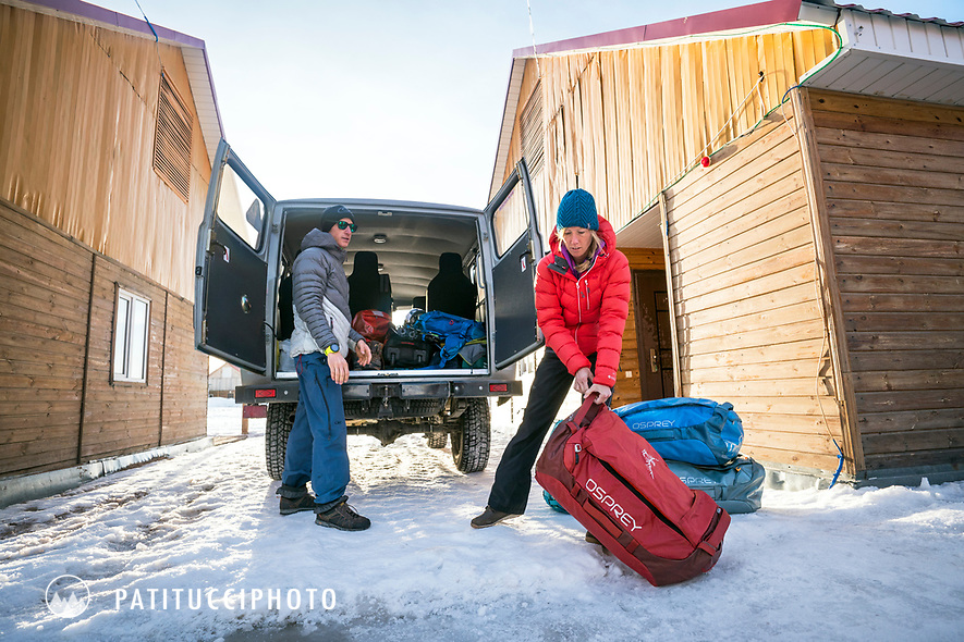 Two skiers load duffel bags into their bus while traveling in Kyrgyzstan