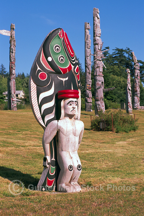 Kwakwaka'wakw (Kwakiutl) Totem Poles, Alert Bay, Cormorant Island, BC, British Columbia, Canada - Memorial Totems on Namgis Burial Grounds - Giant Halibut and Male Figure