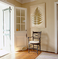 A large framed leaf print hangs above a wooden chair in the entrance to this Connecticut home.