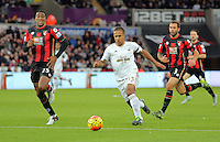 Wayne Routledge of Swansea (C) goes for goal, chased by Sylvain Distin (L) and Steve Cook of Bournemouth  (R) during the Barclays Premier League match between Swansea City and Bournemouth at the Liberty Stadium, Swansea on November 21 2015