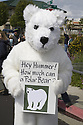 "A man in a polar bear costume holds a sign, ""Hey Hummer! How much can a Polar Bear?"" Calling for fuel efficiencty increases at a Step It Up 2007 rally at a Hummer SUV dealership. San Rafael, California."