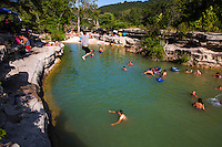 A swimmer leaps off the cliff at Bull Creek District Park. Bull Creek is a great place to cool off during brutal 100 plus degree plus Austin, Texas' summers - Stock Image
