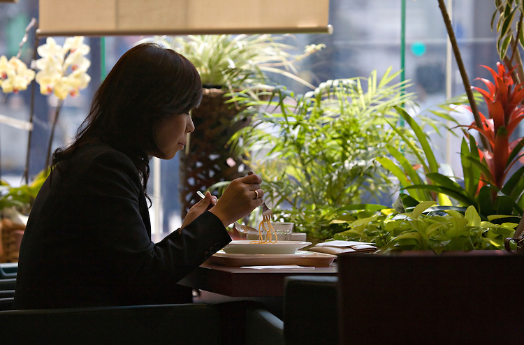Woman eating noodles in cafe in downtown Himeji Japan