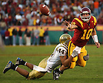USC's John David Booty tries a shovel pass to escape the clutches of UCLA's Bruce Davis at the Los Angeles Memorial Coliseum on December 3, 2005.