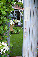 Secret garden door into lawn, gazebo, armillary sundial, climbing Hedera ivy vine, white agapanthus summer flowering bulbs, lawn grass, open blue door with sign saying Private Garden . Board and batten door