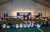 First Lady Michelle Obama speaks as US Soccer Foundation CEO and President Ed Foster-Simeon and  DC United player Jaime Moreno watch during a US Soccer Foundation clinic held at City Center in Washington, DC.