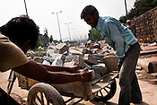Construction workers are seen pushing a cart full of stones on the pavement outside the Jawahar Lal Nehru stadium in New Delhi, India.