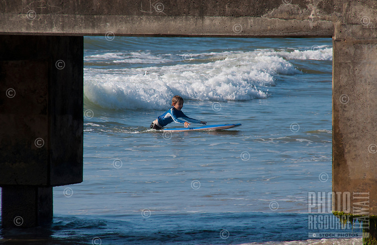 Young boy boogie boarding next to the pier at Hanalei Beach Park on the North Shore of Kauai.